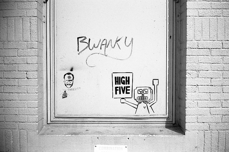 a little roboto with a high five sign, a terry richardson stencil and some graffiti by bwanky