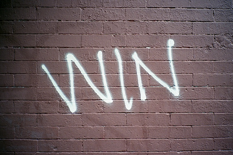 graffiti that reads win on a wall in NYC